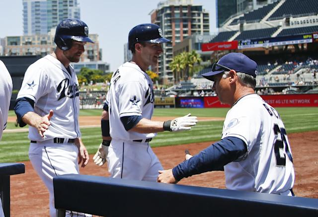 San Diego Padres' Chase Headley, left, and Chris Denorfia, center, are congratulated by manager Bud Black after scoring in the first inning against the Cincinnati Reds in a baseball game on Wednesday, July 2, 2014, in San Diego. (AP Photo/Lenny Ignelzi)