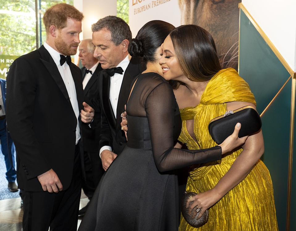 LONDON, ENGLAND - JULY 14: Prince Harry, Duke of Sussex (L) chats with Disney CEO Robert Iger as Meghan, Duchess of Sussex (2nd R) embraces Beyonce Knowles-Carter (R) as they attend the European Premiere of Disney's