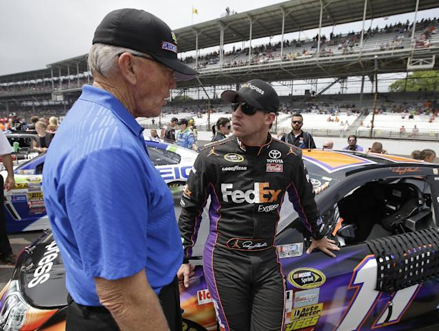 NASCAR team owner Joe Gibbs, left, talks with Denny Hamlin before the Brickyard 400 auto race at Indianapolis Motor Speedway in Indianapolis, Sunday, July 27, 2014. (AP Photo/Darron Cummings)