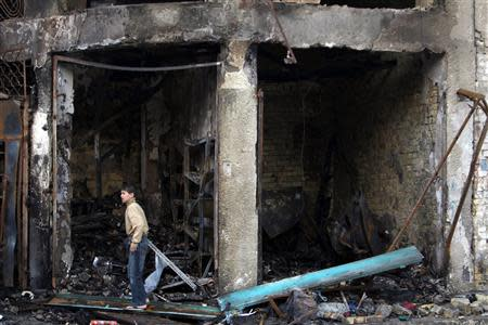 A boy stands at the site of car bomb attack in Baghdad's Karrada district February 18, 2014. REUTERS/Ahmed Saad