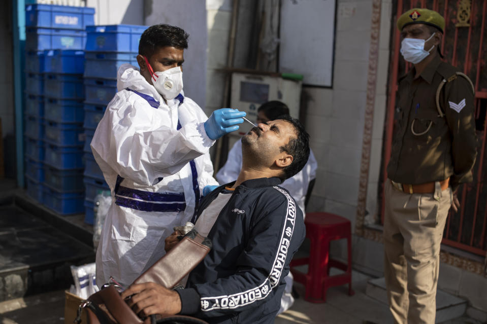A health worker takes a nasal swab sample to test for COVID-19 during random testing of people infront of a shop at Delhi-Noida border on the outskirts of New Delhi, India, Saturday, Nov. 21, 2020. (AP Photo/Altaf Qadri)