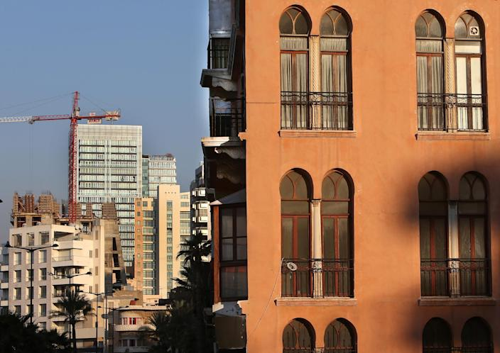 In this February 18, 2014 photo, an old building, right, is overshadowed by newly-built apartment buildings, some still under construction, in Beirut, Lebanon. Lebanon's enchanting Ottoman and colonial French-style buildings once represented Beirut's rich history, withstanding years of civil war and invasions only to be demolished in peace time by wealthy Gulf Arab investors. While Lebanon's real estate sector has developed to become one of the country's success stories, many say it is coming at the expense of Lebanon's identity and heritage. (AP Photo/Hussein Malla)
