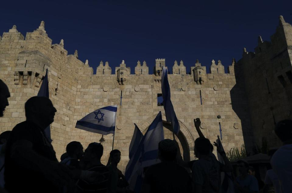 """<span class=""""caption"""">Jewish ultranationalists wave Israeli flags next to the Damascus gate, outside Jerusalem's Old City.</span> <span class=""""attribution""""><span class=""""source"""">(AP Photo/Ariel Schalit)</span></span>"""
