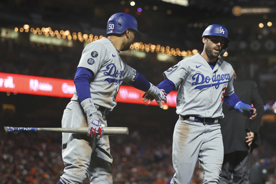 Los Angeles Dodgers' Chris Taylor, right, is congratulated by Mookie Betts after scoring against the San Francisco Giants during the eighth inning of Game 2 of a baseball National League Division Series Saturday, Oct. 9, 2021, in San Francisco. (AP Photo/John Hefti)