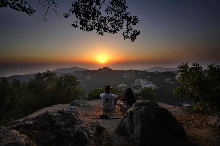 A young couple enjoy the sunset during a hike trip in Chahtoul village, in the Keserwan district, Mount Lebanon Governorate of Lebanon, Sunday, June 27, 2021. With their dollars trapped in the bank, a lack of functioning credit cards and travel restrictions imposed because of the pandemic, many Lebanese who traditionally vacationed over the summer at regional hotspots are also now turning toward domestic tourism. (AP Photo/Hassan Ammar)