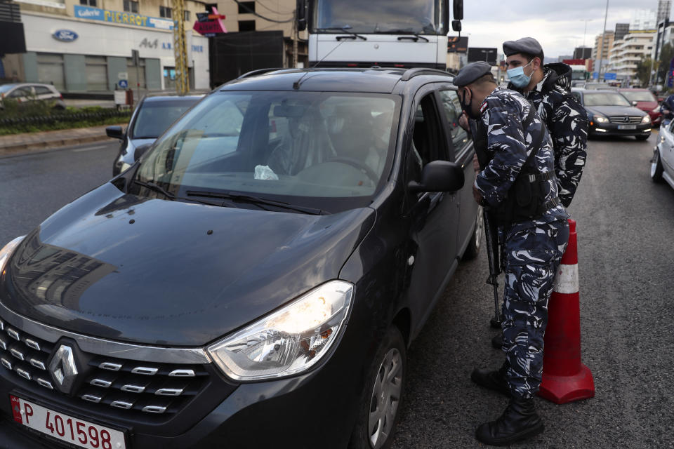 Police officers stand at a checkpoint to inspect cars that violate the lockdown, in Beirut, Lebanon, Thursday, Jan. 14, 2021. Lebanese authorities began enforcing an 11-day nationwide shutdown and round the clock curfew Thursday, hoping to limit the spread of coronavirus infections spinning out of control after the holiday period. (AP Photo / Bilal Hussein)