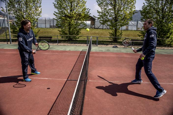In this image take on Friday, April 24, 2020 Italian Tennis Federation coaches Luca Brasi, 55, and his brother Daniele Brasi, 41, practice on their tennis court in Rovetta, near Bergamo, northern Italy. They rely on tourism for about 50% of their yearly income, the rest comes from roughly 900 school students who follow courses throughout the winter, including some 20 under-18 professionals. (AP Photo/Luca Bruno)