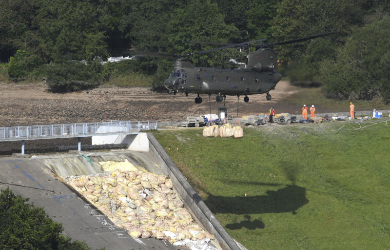 A British Royal Air Force Chinook helicopter transports sandbags as work continues to shore up the dam at Toddbrook Reservoir after it was damaged in heavy rainfall, although dry banks in background show that pumping water from the reservoir has reduced the threat, near the village of Whaley Bridge, England, Tuesday Aug. 6, 2019. The reservoir is being drained to enable inspection and repairs to be carried out while the nearby village of Whaley Bridge has been evacuated because of the threat of inundation from water if the dam breaks. (Joe Giddens/PA via AP)