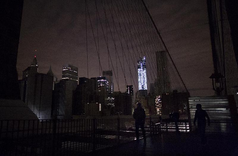 FILE - In this Nov. 1, 2012 file photo, much of lower Manhattan remains dark in the wake of Superstorm Sandy, as viewed from the darkened Manhattan side of the Brooklyn Bridge in New York. 2012 was a year of storms, of raging winds and rising waters, but also broader turbulence that strained our moorings. (AP Photo/Craig Ruttle, File)