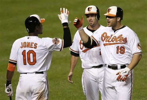 Baltimore Orioles' Adam Jones, left, high-fives Chris Davis (19) after Davis drove in J.J. Hardy, rear, on a home run in the seventh inning of a baseball game against the Pittsburgh Pirates in Baltimore, Wednesday, June 13, 2012. Baltimore won 7-1. (AP Photo/Patrick Semansky)