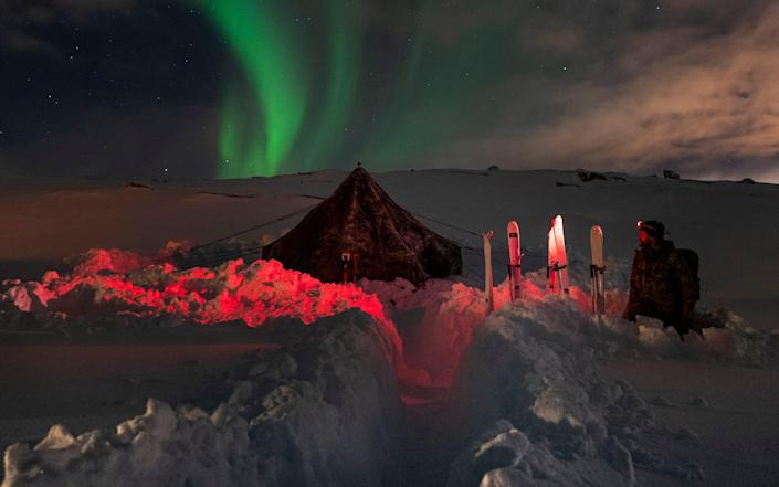 Royal Navy Padre (Russel Fralick) from 45 Commando gazes at the Northern Lights standing next to a ten-man tent wearing a red head torch in Norway, 2021. - LPhot James Clarke/Royal Navy