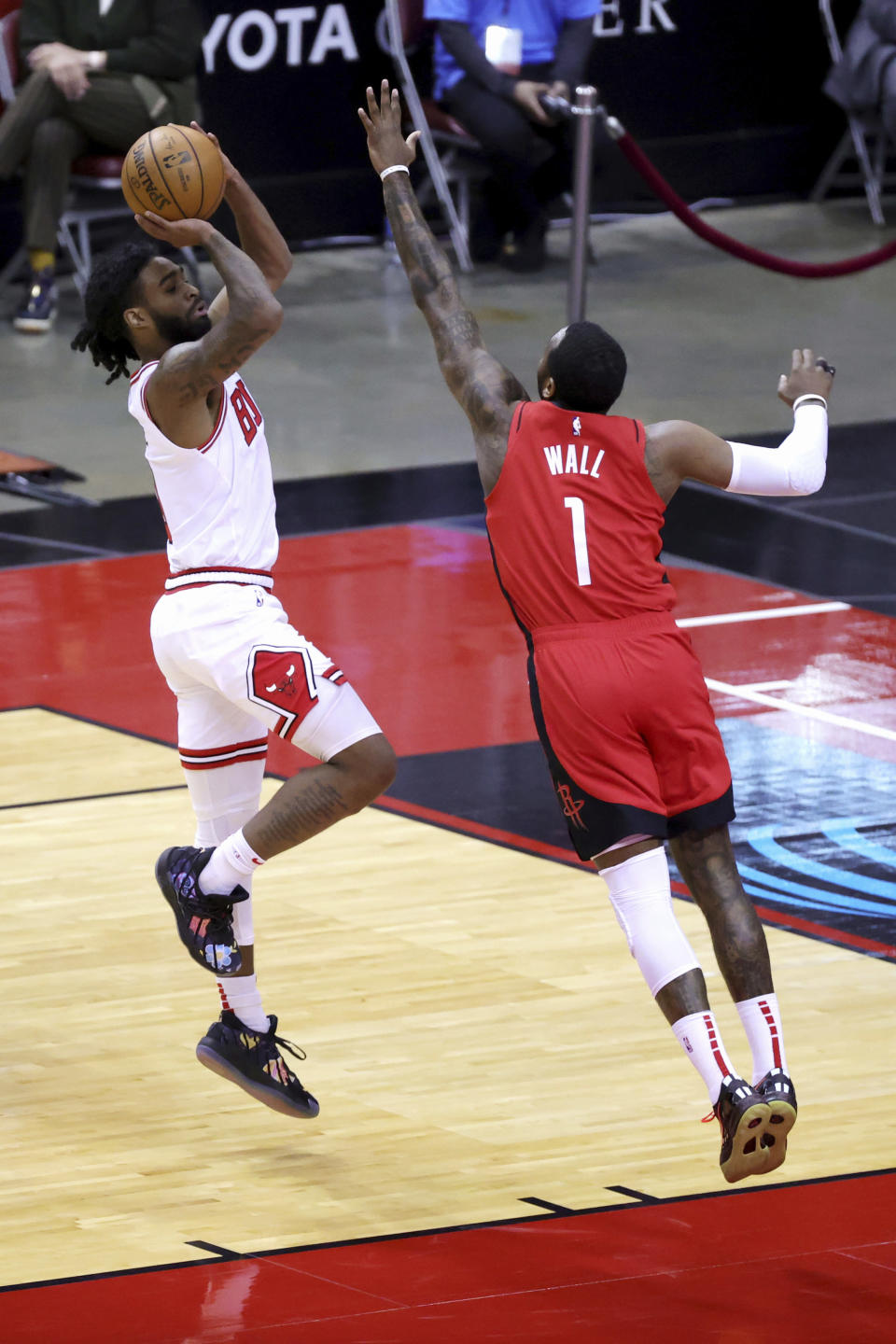 chicago Bulls' Coby White, left, puts up a jump shot ahead of Houston Rockets' John Wall (1) during the first quarter of an NBA basketball game Monday, Feb. 22, 2021, in Houston. (Carmen Mandato/Pool Photo via AP)of an NBA basketball game Monday, Feb. 22, 2021, in Houston. (Carmen Mandato/Pool Photo via AP)