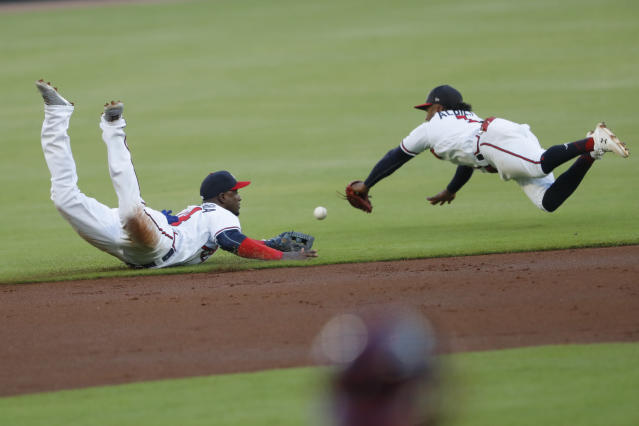 Atlanta Braves shortstop Adeimy Hechavarria, left, and second baseman Ozzie Albies dive for a ball hit for a single by Los Angeles Dodgers' Justin Turner inning of a baseball game Saturday, Aug. 17, 2019, in Atlanta. (AP Photo/John Bazemore)
