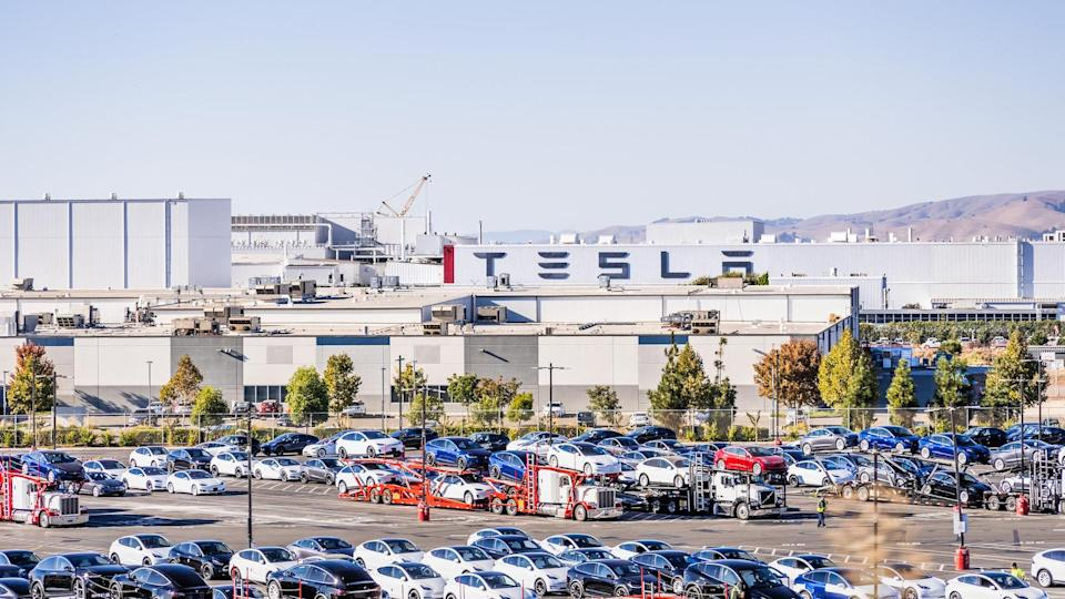 Oct 14, 2020 Fremont / CA / USA - Tesla Factory located in East San Francisco bay area; Large Tesla logo displayed on a building; various Tesla models parked in the factory yard, waiting for delivery