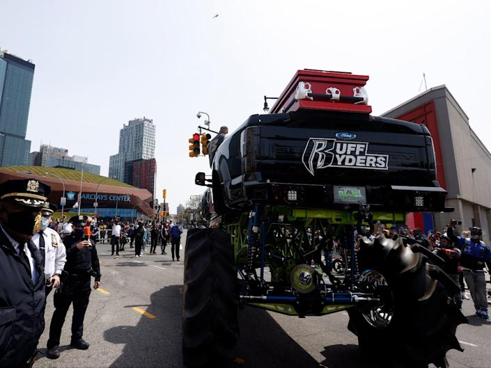 Members of the NYPD stand next to the monster truck holding the casket of US rapper DMX on Flatbush avenue outside the Barclays Center. (EPA)