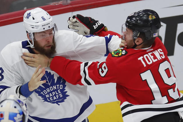 Chicago Blackhawks' Jonathan Toews, right, and Toronto Maple Leafs' Jake Muzzin scuffle during the first period of an NHL hockey game Sunday, Nov. 10, 2019, in Chicago. (AP Photo/Jim Young)