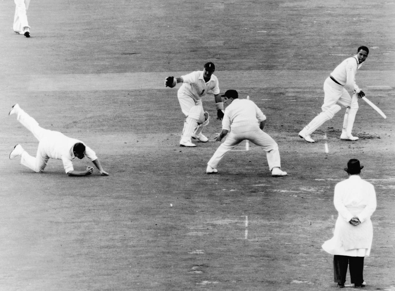 England cricketer Colin Cowdrey (1932 - 2000) goes down to field a shot from Gary Sobers off a ball from Lock jn the final test match against the West Indies at the Oval, 24th August 1957. (Photo by Edward Miller/Keystone/Hulton Archive/Getty Images)