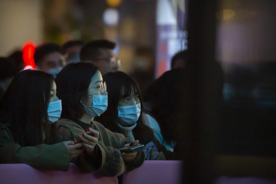 People wearing face masks to protect themselves against the coronavirus watch a livestreamer perform at a shopping mall in Beijing, Friday, Oct. 30, 2020. Chinese authorities are increasingly confident they have contained a COVID-19 outbreak in the country's far western region of Xinjiang. (AP Photo/Mark Schiefelbein)