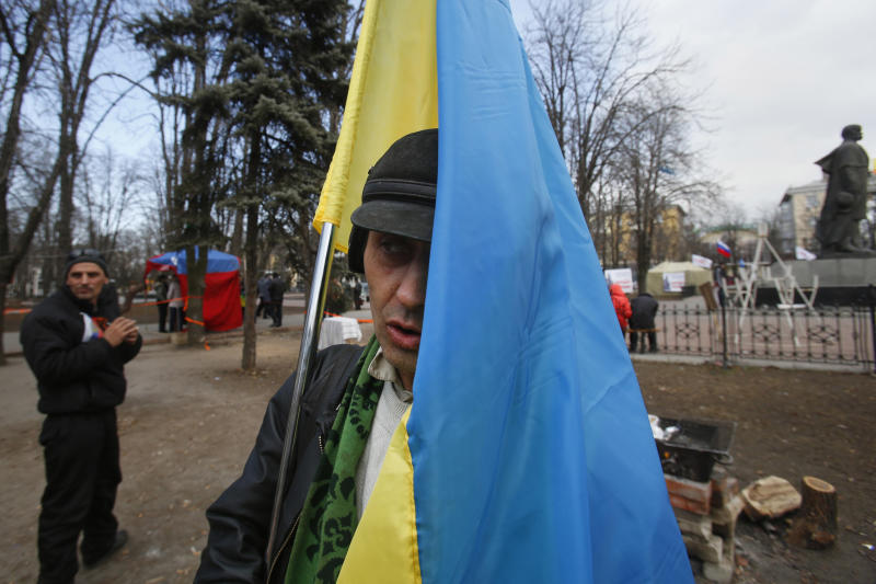 In this photo taken Tuesday, March 11, 2014, pro Russian activists, one of them holding a Ukrainian flag, stand around a camp they set up in Luhansk, eastern Ukraine. In Ukraine's coal-fired industrial east, a potent mix of economic depression, ethnic solidarity and nostalgia for the certainties of the Soviet past among those old enough to remember them have many people demanding the right to become part of Russia as well. (AP Photo/Sergei Grits)