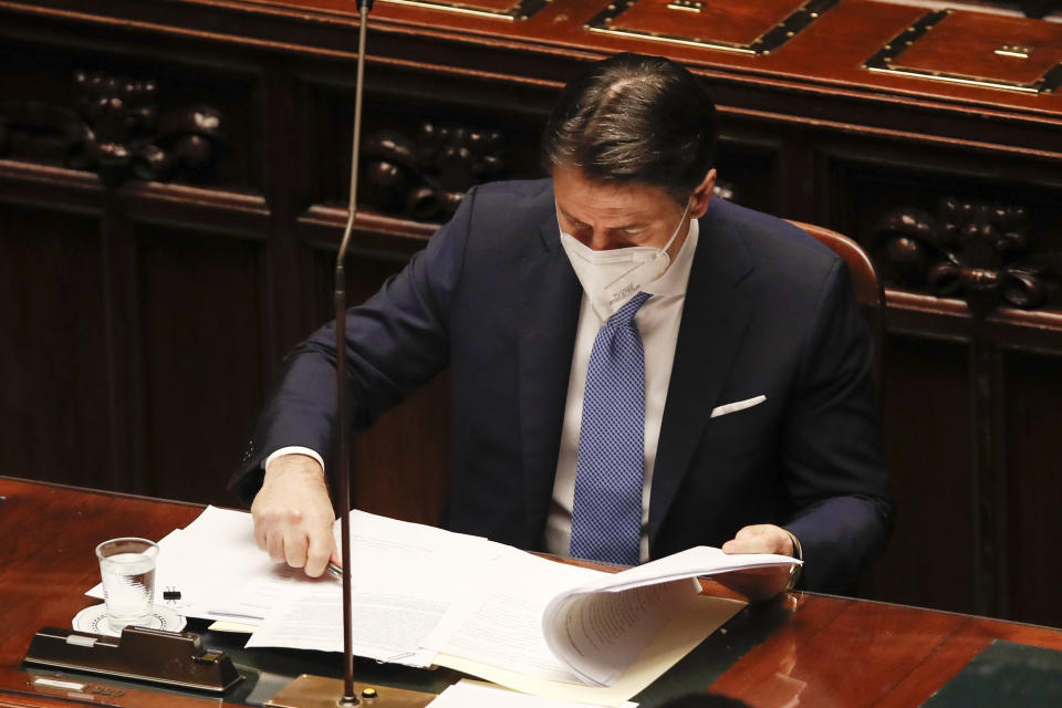 Premier Giuseppe Conte looks at papers prior to delivering his speech at the lower chamber of Parliament, in Rome, Monday, Jan. 18, 2021. Conte fights for his political life with an address aimed at shoring up support for his government, which has come under fire from former Premier Matteo Renzi's tiny but key Italia Viva (Italy Alive) party over plans to relaunch the pandemic-ravaged economy. (AP Photo/Alessandra Tarantino, pool)