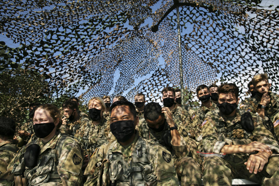 Cadets wear masks as they sit under camouflage netting, Friday, Aug. 7, 2020, in West Point, N.Y. The pandemic is not stopping summer training at the U.S. Military Academy. (AP Photo/Mark Lennihan)