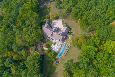 As seen from above, the estate includes an indoor pool with overhead skylight, paved rear courtyard and manicured lawns. Dense foliage surrounds the estate for added privacy. NewJerseyLuxuryAuction.com.