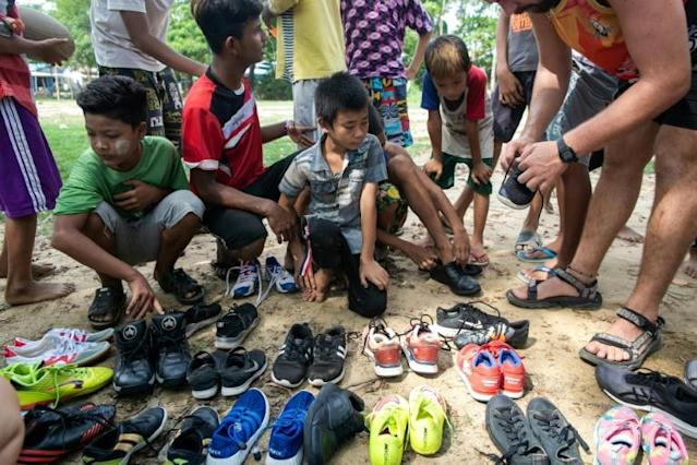 If the shoe fits: Little Dragons rugby players choose from pairs of donated secondhand trainers -- though many still play barefoot (AFP Photo/Sai Aung MAIN)