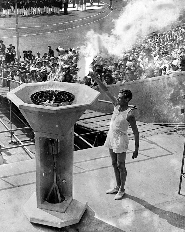 British athlete John Mark lights the Olympic Flame from the Olympic Torch, during the opening ceremony of the XIV Olympiad, in Wembley Stadium, London, July 29, 1948. (AP Photo)