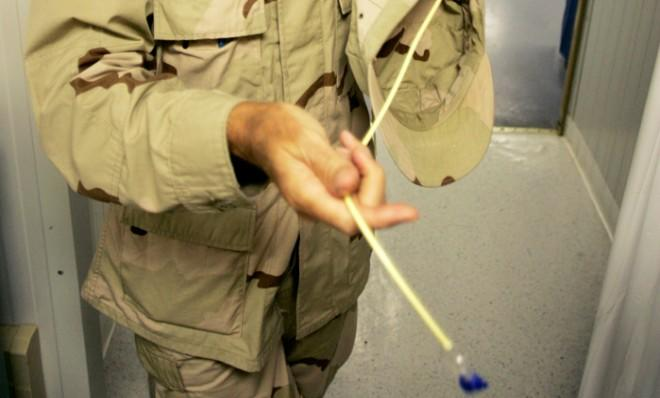 A senior medical doctor holds a feeding tube as he explains the treatment of the hunger strike detainees at Camp David, Guantanamo Bay.