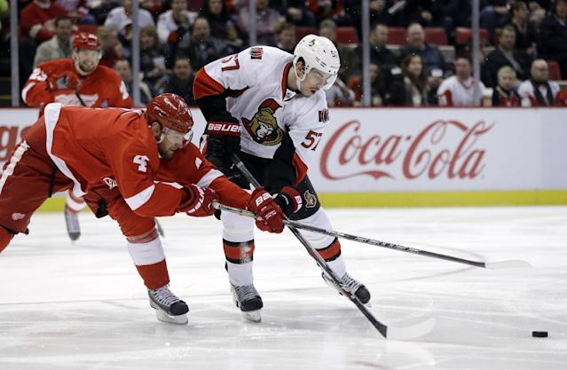 Detroit Red Wings defenseman Jakub Kindl (4) of the Czech Republic and Ottawa Senators center Derek Grant (57) reach for the puck during the first period of an NHL hockey game in Detroit, Saturday, Nov. 23, 2013. (AP Photo/Carlos Osorio)