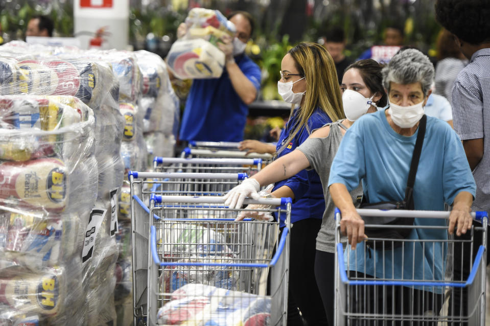 BELO HORIZONTE, BRAZIL - MARCH 31: People wearing protective masks queue for food packages at a local market on March 31, 2020 in Belo Horizonte, Brazil. Belo Horizonte city council started to distribute food packages to families of students enrolled in municipal schools. The initiative was developed to replace school meals, since classes are suspended due to the coronavirus (COVID-19). The distribution will last as long as classes are suspended, and each family will receive one package per month. (Photo by Pedro Vilela/Getty Images)