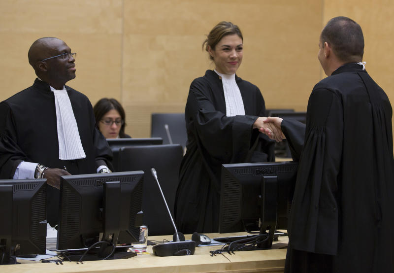 Representatives of the Office of Public Counsel for the Defence, Xavier-Jean Keita, left, and Melinda Taylor, center, shake hands with Professor Phillippe Sands of the Representatives of Libya, right, at the start of a hearing in the International Criminal Court (ICC) in The Hague Tuesday Oct. 9, 2012. The International Criminal Court is holding a two-day hearing into where the eldest son of former Libyan dictator Moammar Gadhafi should be put on trial. Seif al-Islam Gadhafi is charged by the international court with crimes against humanity for his alleged involvement in the deadly crackdown on dissent against his father's rule. However Libyan authorities say they want to prosecute him at home, where he is being held. (AP Photo/Michael Kooren, POOL)