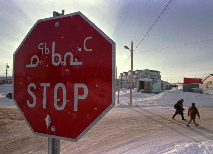 A stop sign written in both English and the traditional Inuit language of Inuktitut is seen in the eastern Arctic community of Iqaluit, NWT, Photo from The Canadian Press