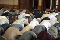 """Muslims offer Eid al-Adha prayers as a boy stands in Kabul, Afghanistan, Tuesday, July 20, 2021. Eid al-Adha, or """"Feast of the Sacrifice,"""" commemorates the Quranic tale of Prophet Ibrahim's willingness to sacrifice his son as an act of obedience to God. (AP Photo/Rahmat Gul)"""