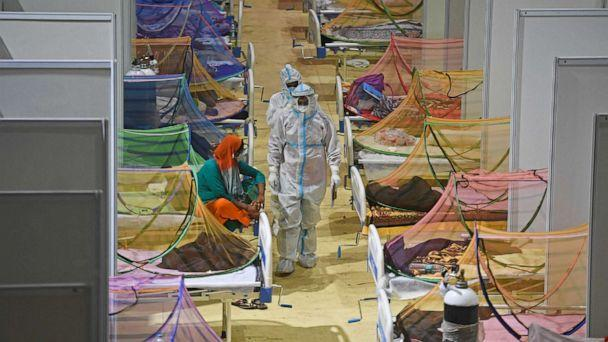 PHOTO: Health workers wearing personal protective equipment suits attend to COVID-19 coronavirus patients inside a temporary COVID care facility in New Delhi on May 2, 2021. (Tauseef Mustafa/AFP via Getty Images)