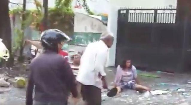 A man in the street is seen trying to help an injured lady. Photo: YouTube