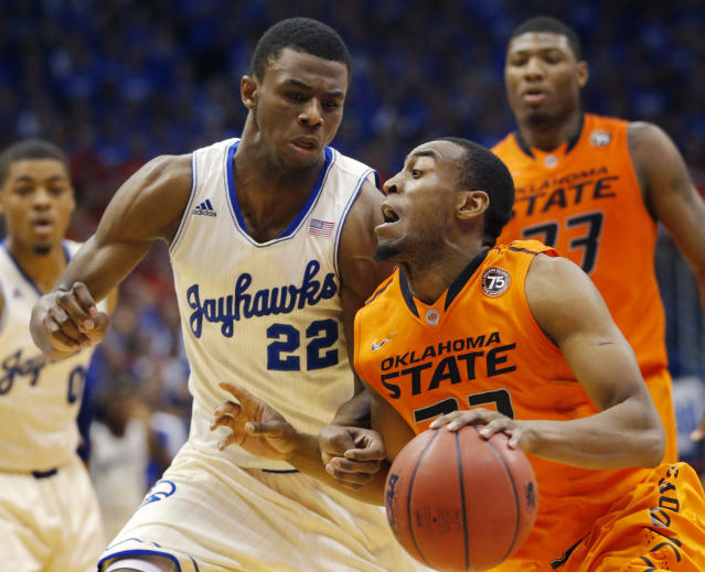 Oklahoma State guard Markel Brown, right, is fouled by Kansas guard Andrew Wiggins (22) during the second half of an NCAA college basketball game at Allen Fieldhouse in Lawrence, Kan., Saturday, Jan. 18, 2014. Kansas defeated Oklahoma State 80-78. (AP Photo/Orlin Wagner)