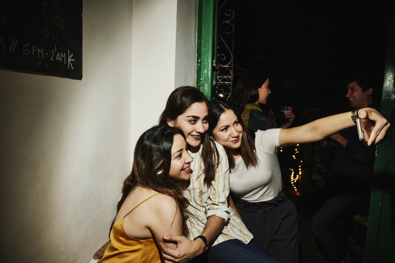 Smiling female friends taking selfie with smart phone while hanging out in night club