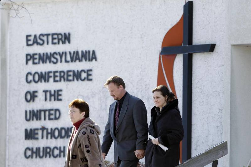 Accompanied by his wife Brigitte, right, the Rev. Frank Schaefer, of Lebanon, Pa., center, departs after a meeting with officials at the Eastern Pennsylvania Conference of the United Methodist Church, Thursday, Dec. 19, 2013, in Norristown, Pa. Church officials have defrocked Schaefer, who officiated his son's gay wedding in Massachusetts. (AP Photo/Matt Rourke)