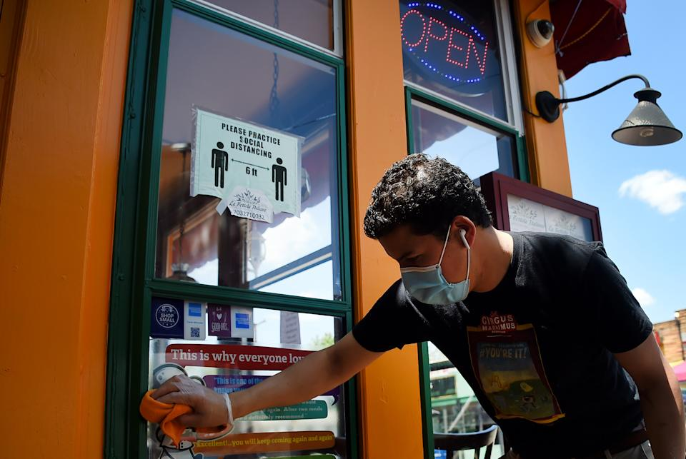 An employee wearing gloves and a face mask cleans up a restaurant in the Crystal City neighborhood of Arlington, Virginia, as restaurants and businesses try to adapt to the ever-changing situation amid the coronavirus pandemic, on May 13, 2020. (Photo by Olivier DOULIERY / AFP) (Photo by OLIVIER DOULIERY/AFP via Getty Images)