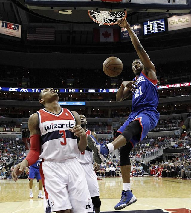 Philadelphia 76ers forward Thaddeus Young (21) dunks over Washington Wizards guard Bradley Beal (3) and forward Trevor Booker (35) in the first half of an NBA basketball game, Friday, Nov. 1, 2013, in Washington. (AP Photo/Alex Brandon)
