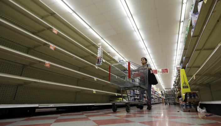<p>Shoppers pass empty shelves along the bottled water aisle in a Houston grocery store as Hurricane Harvey intensifies in the Gulf of Mexico, Thursday, Aug. 24, 2017. (Photo: David J. Phillip/AP) </p>