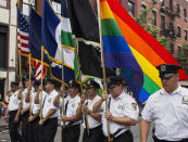FILE - Members of the New York City Police Department carry flags, including one with the rainbow colors, during New York's Gay Pride Parade, June 30, 2013, in New York. As Pride weekend approaches, the recent decision by organizers of New York City's event to ban LGBTQ police officers from marching in future parades while wearing their uniforms has put a spotlight on issues of identity and belonging, power and marginalization. (AP Photo/Craig Ruttle, File)