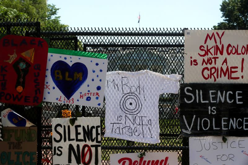 FILE PHOTO: Protest signs are affixed to the security fence around Lafayette Square at the scene where protesters clashed with police near the White House in Washington