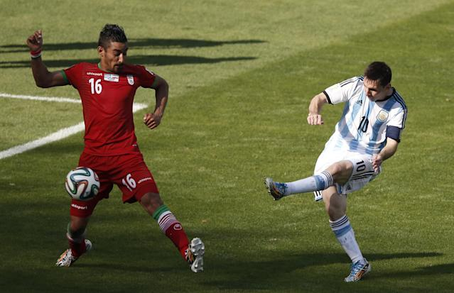Argentina's forward and captain Lionel Messi (R) shoots past Iran's forward Reza Ghoochannejhad at the Mineirao Stadium in Belo Horizonte during their teams' World Cup match on June 21, 2014 (AFP Photo/Adrian Dennis)