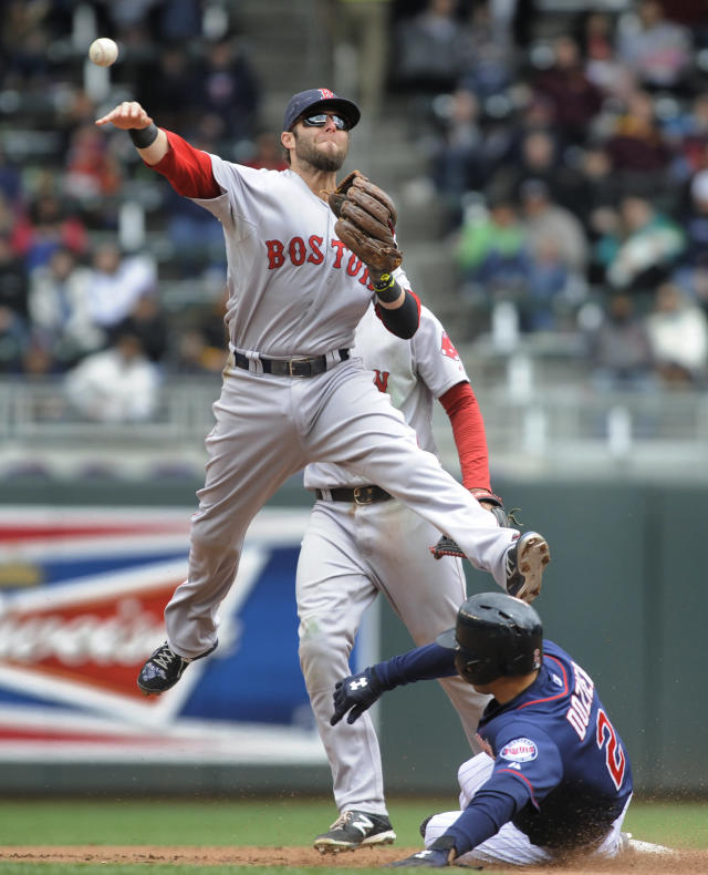 Boston Red Sox second baseman Dustin Pedroia, left, sails over the Minnesota Twins' Brian Dozier, right, after getting the force at second during the fourth inning of a baseball game in Minneapolis, Thursday, May 15, 2014. (AP Photo/Tom Olmscheid)