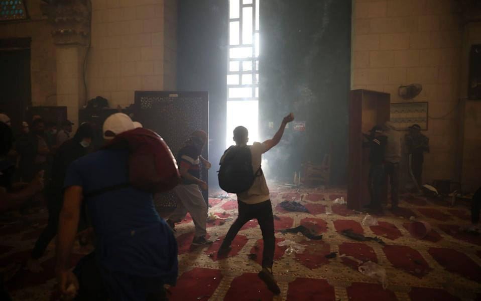 Palestinians inside the Al-Aqsa mosque clash with Israeli security forces at the Al Aqsa Mosque compound in Jerusalem's Old City Monday, May 10, 2021 - Mahmoud Illean/AP