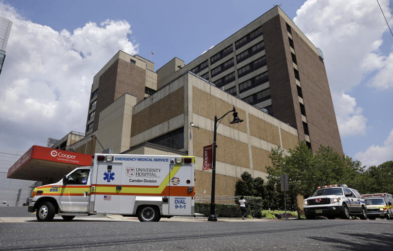 University Hospital, Camden Division, ambulances and emergency trucks rush to the emergency room at Cooper University Hospital Tuesday, July 7, 2015, in Camden, N.J. New Jersey Gov. Chris Christie has signed a bill that will overhaul who runs emergency paramedic services in the city of Camden. Currently, the Newark-based University Hospital provides ambulances in the city, while the Marlton-based Virtua provides paramedics, who provide care for patients but not transportation. The new law will give the state's three, including Cooper, Level 1 trauma centers exclusive rights to provide both kinds of emergency medical services in their cities. (AP Photo/Mel Evans)