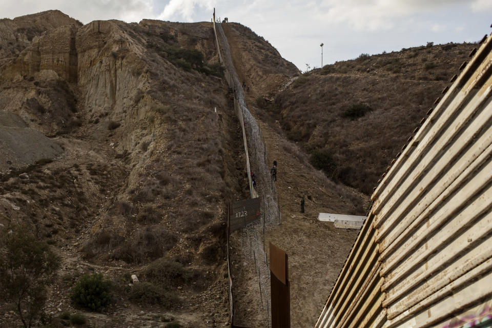 The border wall between Mexico and US on December 1, 2018. Honduran migrants are trapped between the wall and the barber wire in US territory. (Photo: Fabio Bucciarelli for Yahoo News)