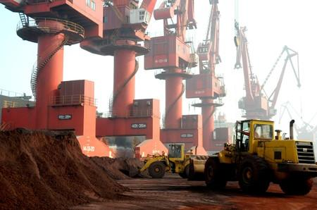 Workers transport soil containing rare earth elements for export at a port in Lianyungang